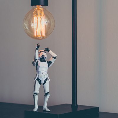 Storm Trooper action figure from Star Wars reaching up to lightbulb and idea